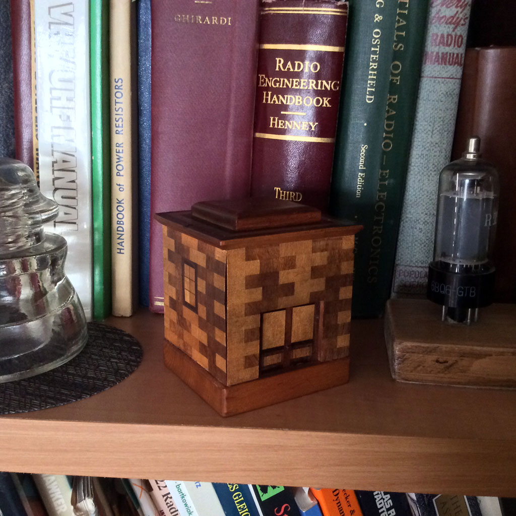 Japanese Puzzle Bank  (1960)<br />Japanese puzzle bank with very nice wood marquetry. Has a simple trick opening. Also shown are various books in my collection. : Figure 98 :