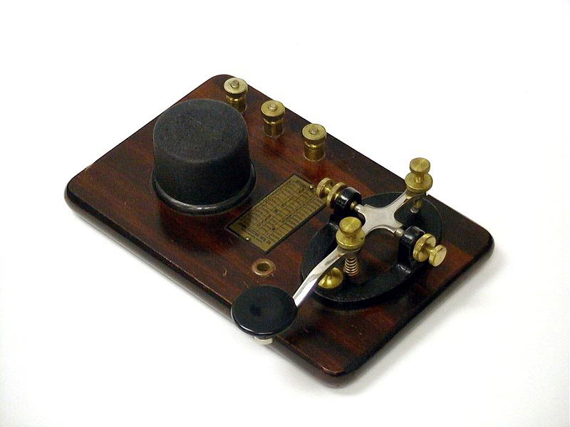 Signal KOB (1945)<br />Telegraph Key and Buzzer on base. Brass hardware, steel lever key with black cast iron base mounted on a wooden base with a round black buzzer. Morse Code brass plate. Wiring diagram on the bottom. : Figure 57 :